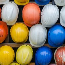 A variety of different hard hats that environmental consultants wear lined up in multiple rows