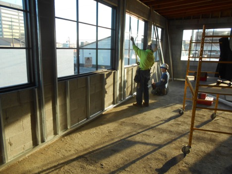 construction worker installing window in community room