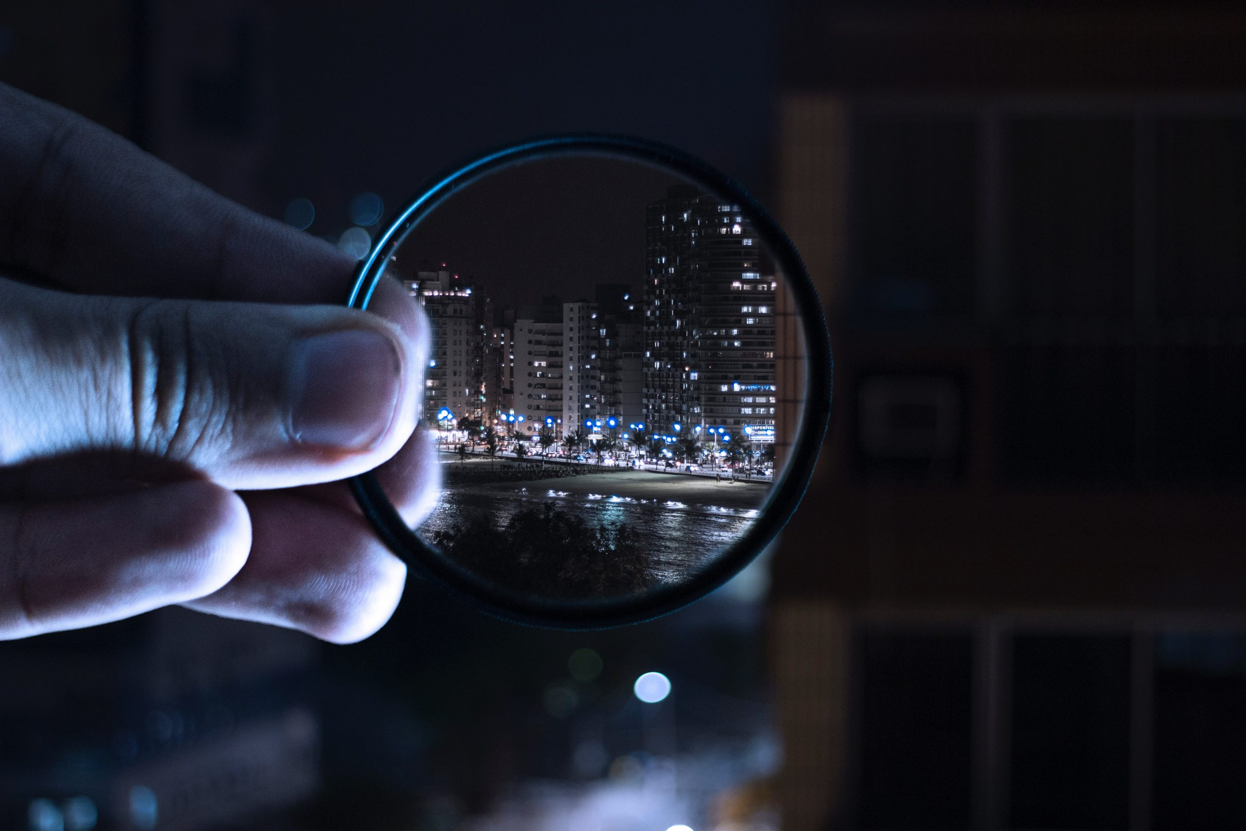 Insurance archeologist holding magnifying glass up at nigh time cityscape