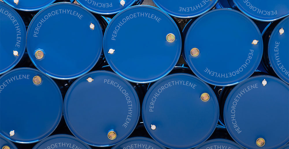 Blue drums filled with perc or perchloroethylene stacked on top of one another