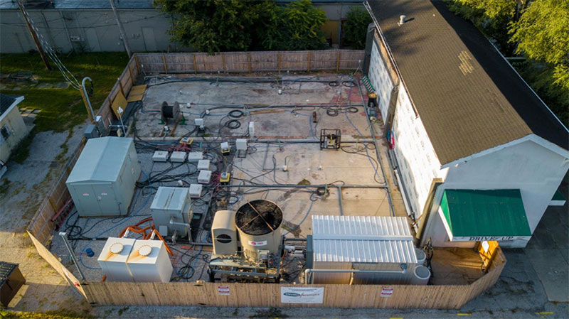 Aerial view of fenced in thermal remediation system behind an old drycleaning building