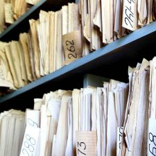 old files on shelves found during insurance archeology