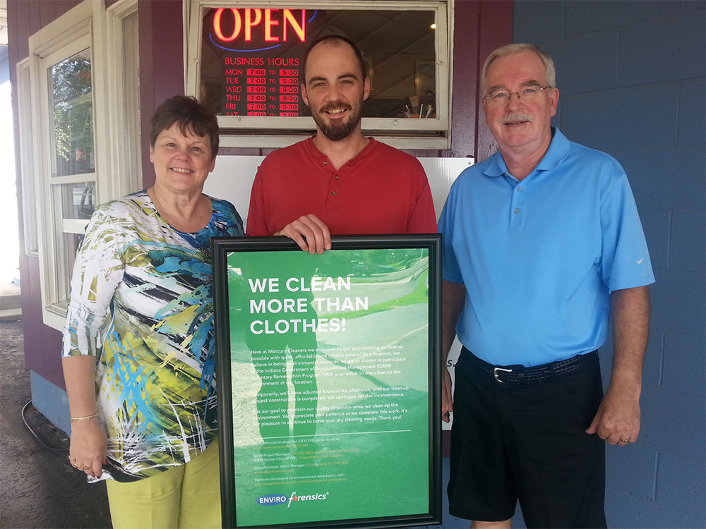 The Dygert Family, owners of Mercury Cleaners holding sign in front of business promoting their environmental remediation efforts