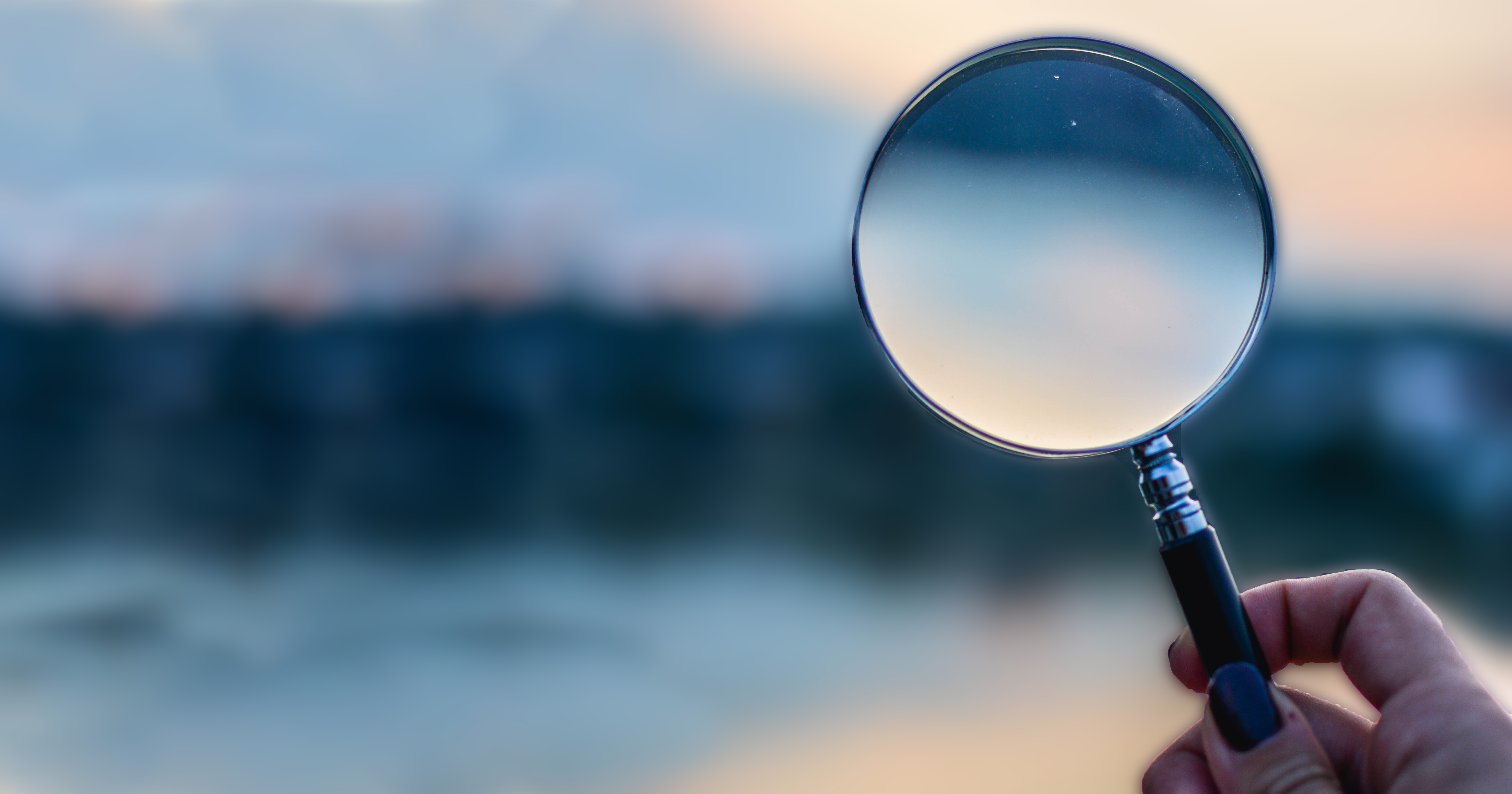 Picture of hand holding a magnifying glass in front of obscure environment