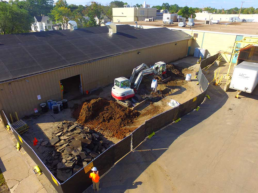 Aerial view of the remedial method of soil excavation outside of an industrial warehouse