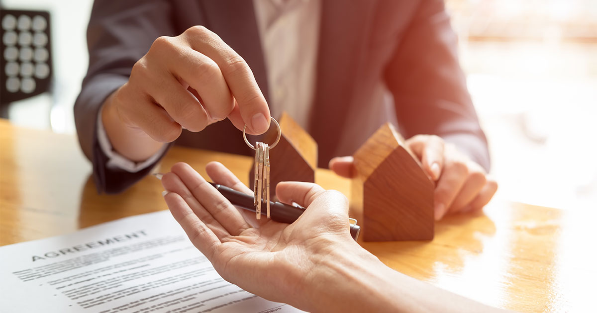 Person handing keys to a drycleaning property over to new property owners