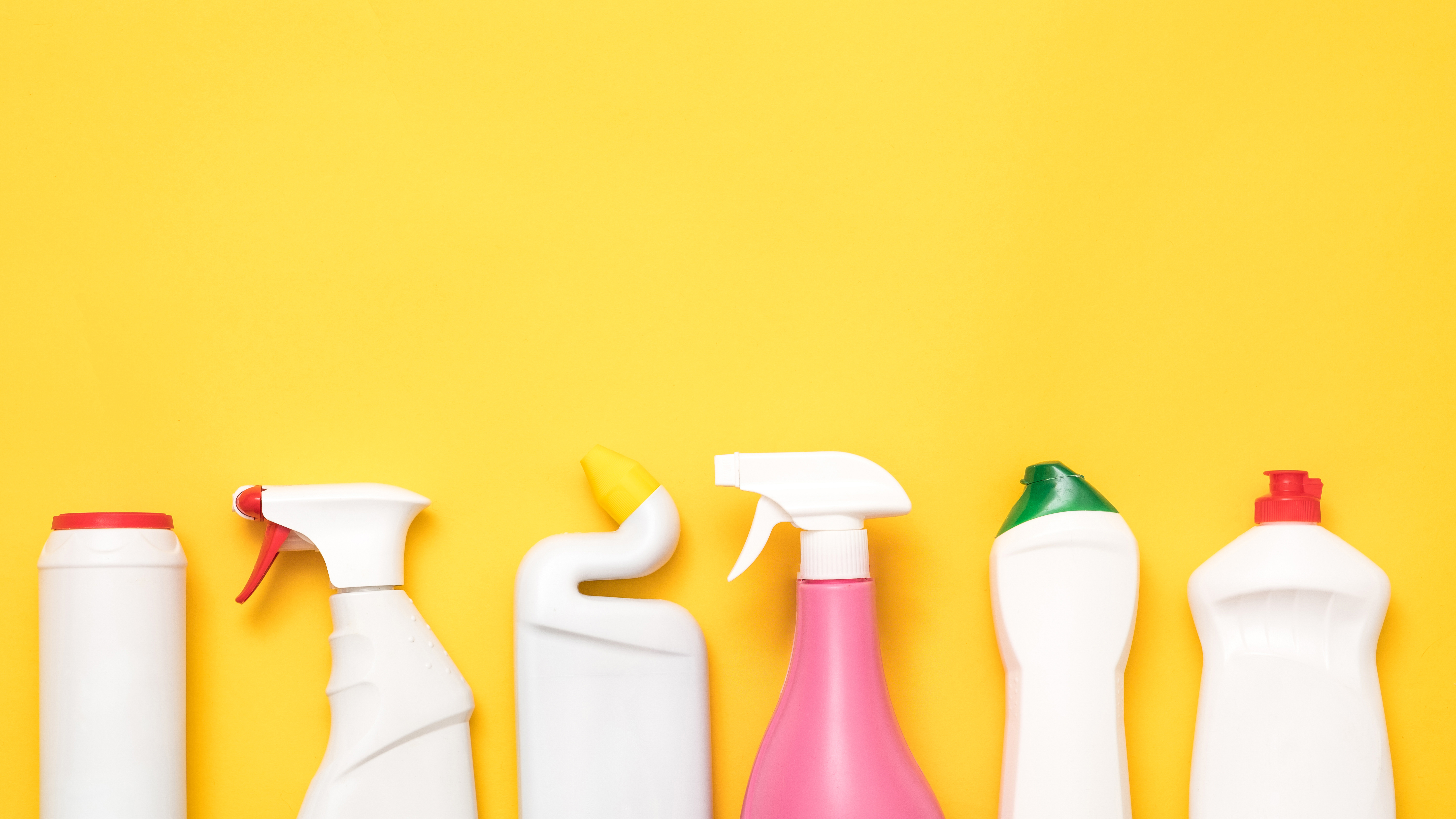 Cleaning products that contain PFAS in front of yellow background