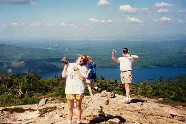 Picture of woman holding rock with older man holding arms up while standing on a rocky hill overlooking a body of water and trees in Acadia National Park