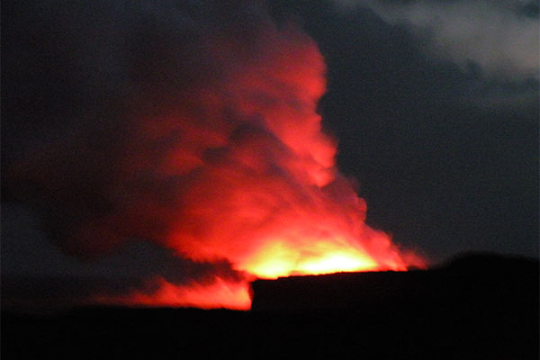 Picture of glowing orange and red cloud turning into steam at Hawaiʻi Volcanoes National Park