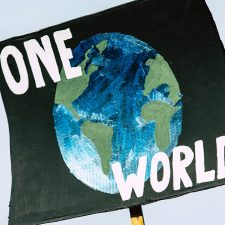 Picture of protest sign with the words one world on it