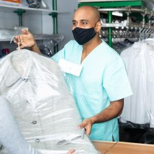 drycleaner with mask handing clean clothes to customer