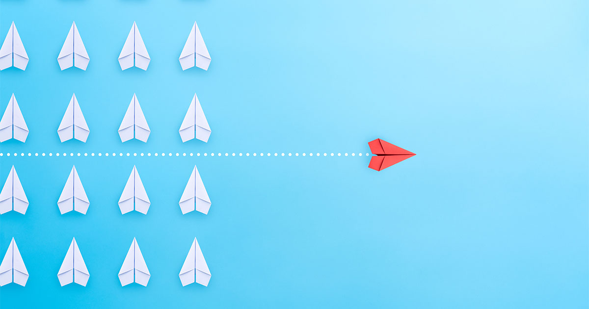 A red paper air plane moving forward with a new strategy away from a group of white paper air planes