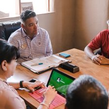 Drycleaner sitting at table negotiating sale of property and business