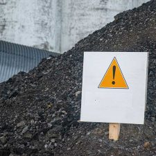 caution sign in pile of perc contaminated soil
