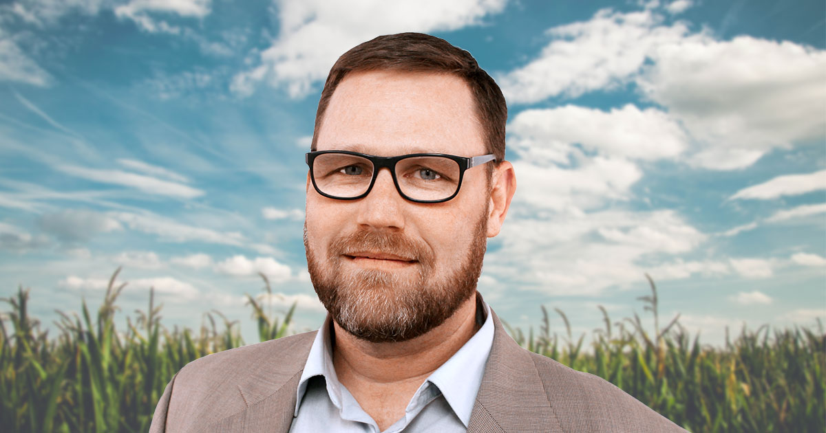 Headshot of Rob Hoverman in front of sunlit cornfield