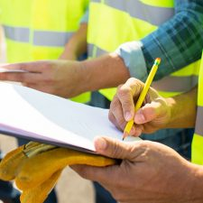 Environmental consultants in safety vests conducting real estate due diligence with clipboard