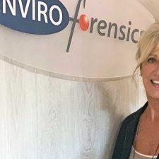 Account Specialist Karen Trotter standing in front of EnviroForensics sign