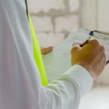 Environmental consultant wearing yellow safety vest writing notes on a clipboard during a Phase I Environmental Site Assessment
