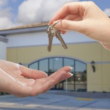 Landlord hand handing keys to tenant hand in front of commercial retail space